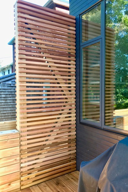 Privacy screen with vertical wood strips on backyard deck.